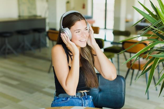 Mulher jovem e bonita ouvindo música dentro de casa