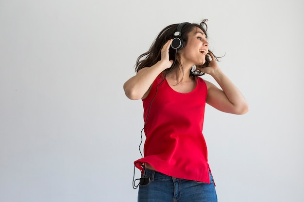 Mulher jovem e bonita ouvindo música no seu celular com fone de ouvido e se divertindo sobre branco