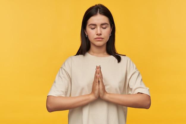 Mulher jovem e bonita pacífica com cabelo escuro e olhos fechados, camiseta branca mantém as mãos em posição de oração e meditando sobre a parede amarela
