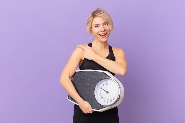 Mulher jovem e bonita parecendo animada e surpresa, apontando para o lado. conceito de dieta
