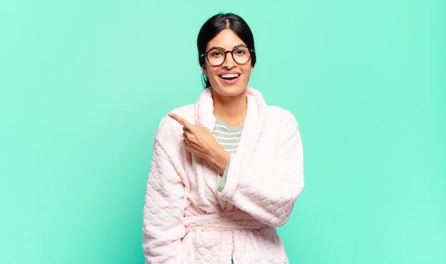 Mulher jovem e bonita parecendo animada e surpresa, apontando para o lado e para cima para copiar o espaço. conceito de pijama