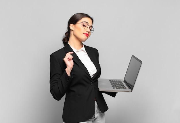 Mulher jovem e bonita parecendo arrogante, bem-sucedida, positiva e orgulhosa, apontando para si mesma. conceito de laptop