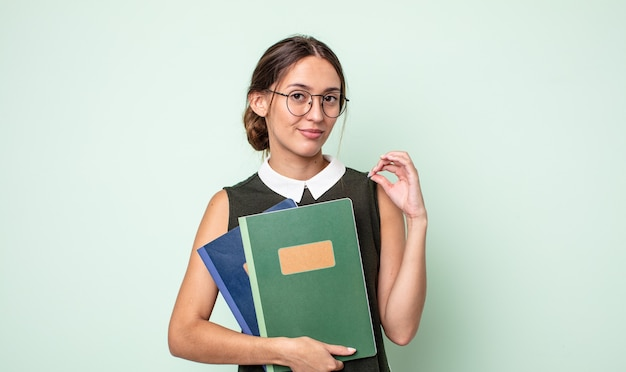 Mulher jovem e bonita parecendo arrogante, bem-sucedida, positiva e orgulhosa. conceito universitário