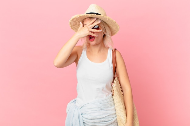 Mulher jovem e bonita parecendo chocada, assustada ou apavorada, cobrindo o rosto com a mão. conceito de turista de verão