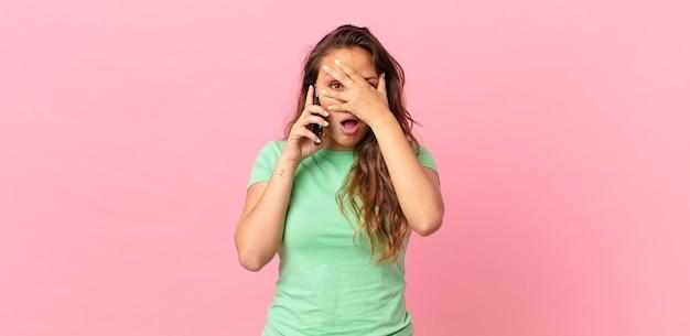 Mulher jovem e bonita parecendo chocada, assustada ou apavorada, cobrindo o rosto com a mão e segurando um telefone inteligente