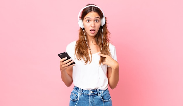 Mulher jovem e bonita parecendo chocada e surpresa com a boca bem aberta, apontando para si mesma com fones de ouvido e um smartphone