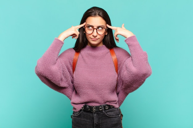 Mulher jovem e bonita parecendo concentrada e pensando seriamente em uma ideia, imaginando uma solução para um desafio