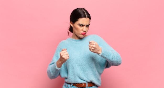 Mulher jovem e bonita parecendo confiante, zangada, forte e agressiva, com punhos prontos para lutar em posição de boxe
