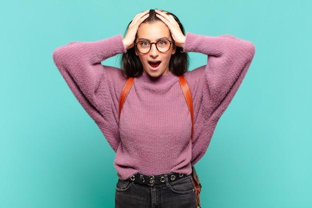 Mulher jovem e bonita parecendo desagradavelmente chocada, assustada ou preocupada, com a boca bem aberta e cobrindo as duas orelhas com as mãos. conceito de estudante
