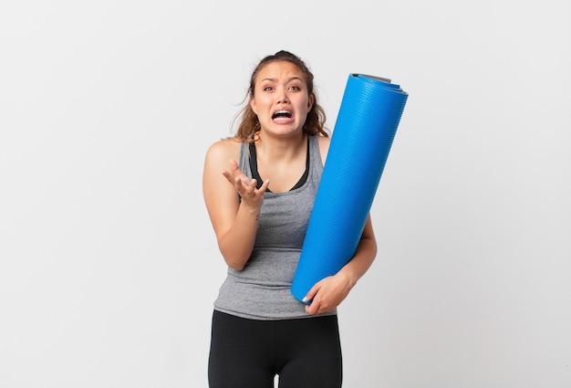 Mulher jovem e bonita parecendo desesperada, frustrada e estressada segurando um tapete de ioga