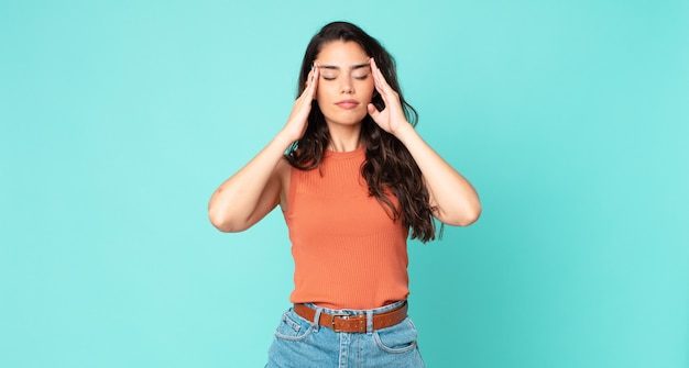 Mulher jovem e bonita parecendo estressada e frustrada, trabalhando sob pressão, com dor de cabeça e preocupada com problemas