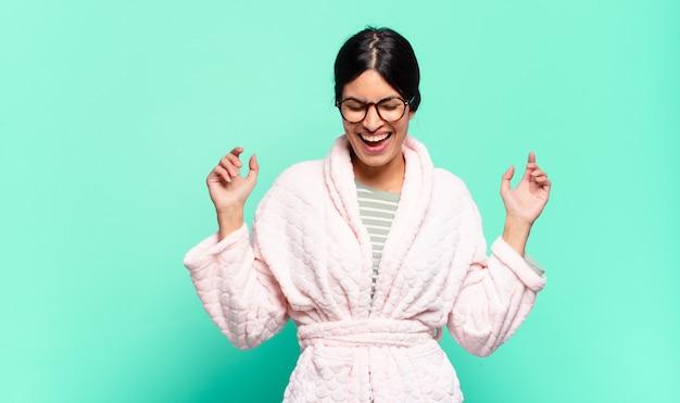 Mulher jovem e bonita parecendo extremamente feliz e surpresa, comemorando o sucesso, gritando e pulando. conceito de pijama