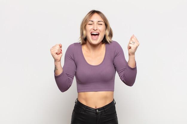 Mulher jovem e bonita parecendo extremamente feliz e surpresa, comemorando o sucesso, gritando e pulando