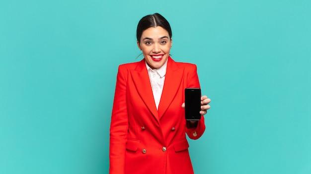 Mulher jovem e bonita parecendo feliz e agradavelmente surpresa, animada com uma expressão fascinada e chocada. conceito de telefone inteligente