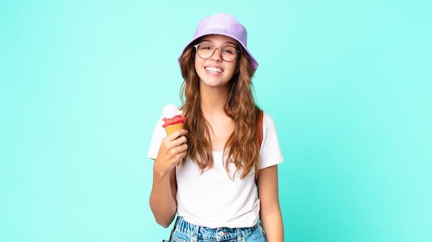 Mulher jovem e bonita parecendo feliz e agradavelmente surpresa segurando um sorvete. conceito de verão