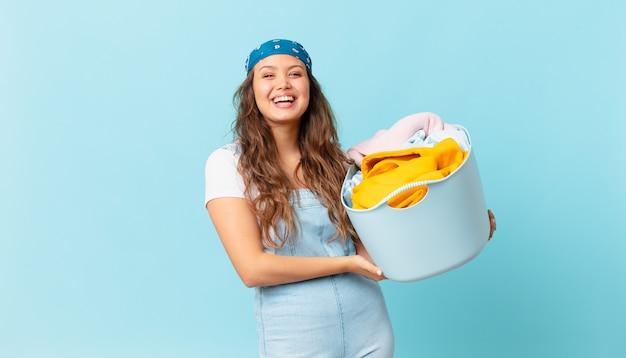 Mulher jovem e bonita parecendo feliz e agradavelmente surpresa, segurando uma cesta de roupas para lavar