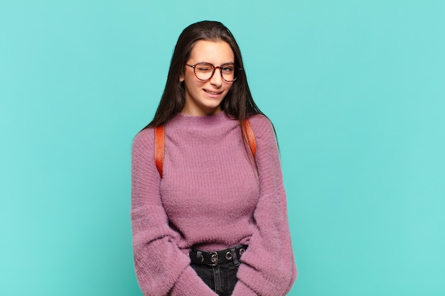 Mulher jovem e bonita parecendo feliz e amigável, sorrindo e piscando os olhos para você com uma atitude positiva. conceito de estudante
