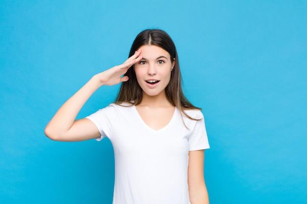 Mulher jovem e bonita parecendo feliz, espantada e surpresa, sorrindo e percebendo uma boa notícia incrível contra a parede azul