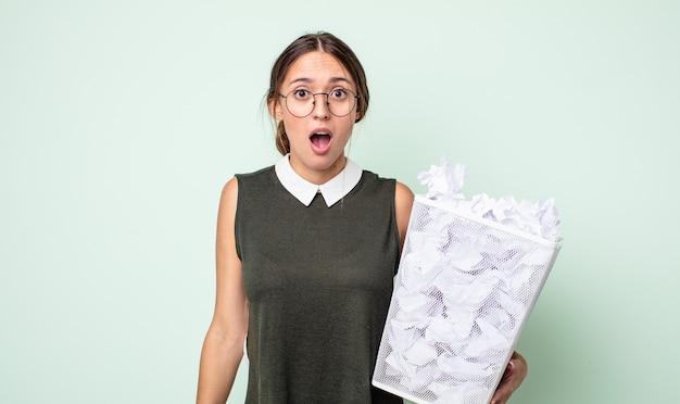 Mulher jovem e bonita parecendo muito chocada ou surpresa. conceito de lixo de bolas de papel