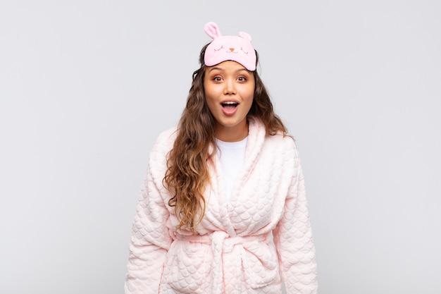 Mulher jovem e bonita parecendo muito chocada ou surpresa, olhando com a boca aberta dizendo uau de pijama