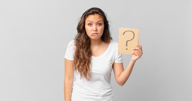 Mulher jovem e bonita parecendo perplexa e confusa e segurando um sinal de interrogação