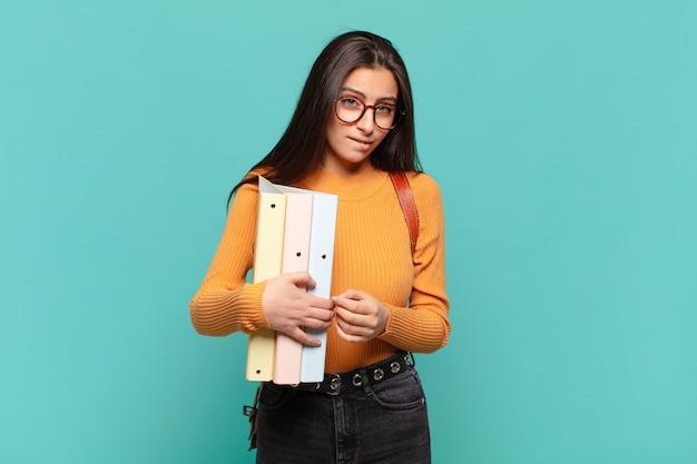 Mulher jovem e bonita parecendo perplexa e confusa, mordendo o lábio com um gesto nervoso, sem saber a resposta para o problema. conceito de estudante