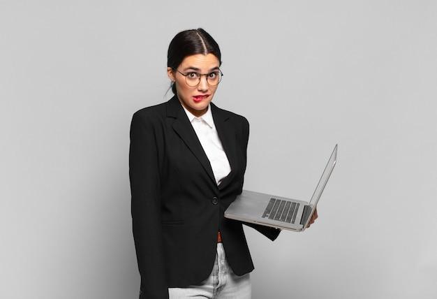 Mulher jovem e bonita parecendo perplexa e confusa, mordendo o lábio com um gesto nervoso, sem saber a resposta para o problema. conceito de laptop
