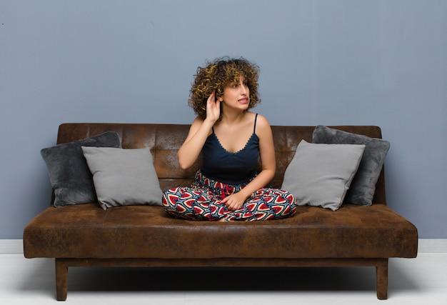 Mulher jovem e bonita parecendo séria e curiosa, ouvindo, tentando ouvir uma conversa secreta ou fofoca, bisbilhotando sentado em um sofá.