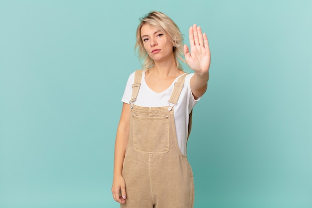 Mulher jovem e bonita parecendo séria, mostrando a palma da mão aberta fazendo gesto de pare
