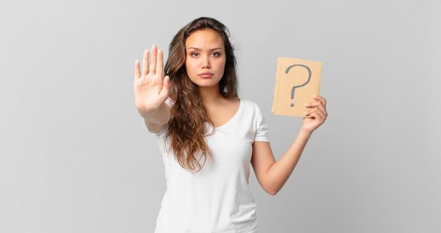 Mulher jovem e bonita parecendo séria, mostrando a palma da mão aberta fazendo um gesto de pare e segurando um sinal de interrogação