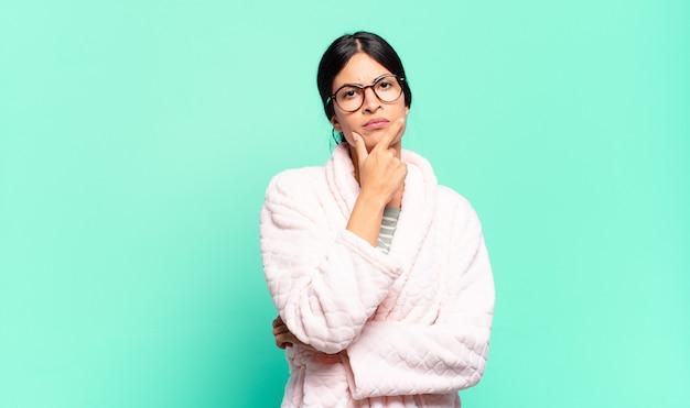 Mulher jovem e bonita parecendo séria, pensativa e desconfiada, com um braço cruzado e a mão no queixo, opções de ponderação. conceito de pijama
