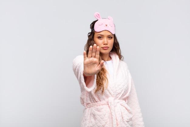 Mulher jovem e bonita parecendo séria, severa, descontente e irritada mostrando a palma da mão aberta fazendo gesto de pare usando pijama