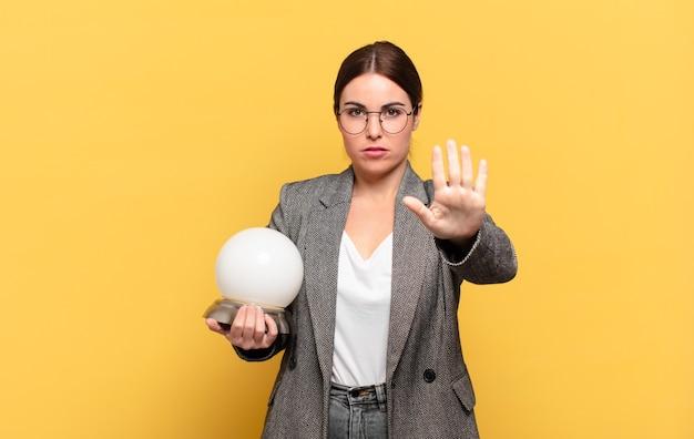 Mulher jovem e bonita parecendo séria, severa, descontente e irritada mostrando a palma da mão aberta fazendo gesto de pare