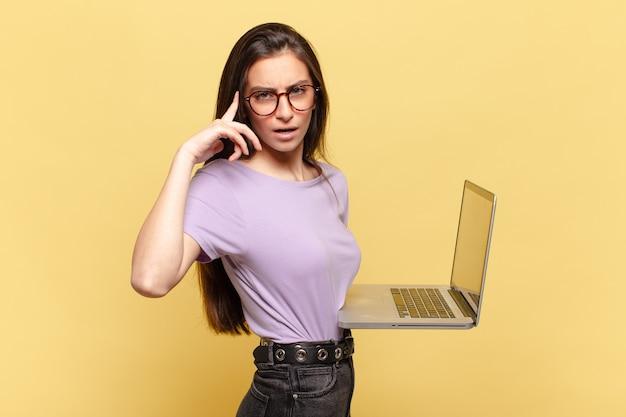 Mulher jovem e bonita parecendo surpresa, boquiaberta, chocada, percebendo um novo pensamento, ideia ou conceito. conceito de laptop