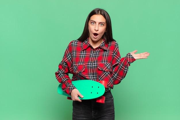 Mulher jovem e bonita parecendo surpresa e chocada, com o queixo caído segurando um objeto com a mão aberta na lateral. conceito de skate