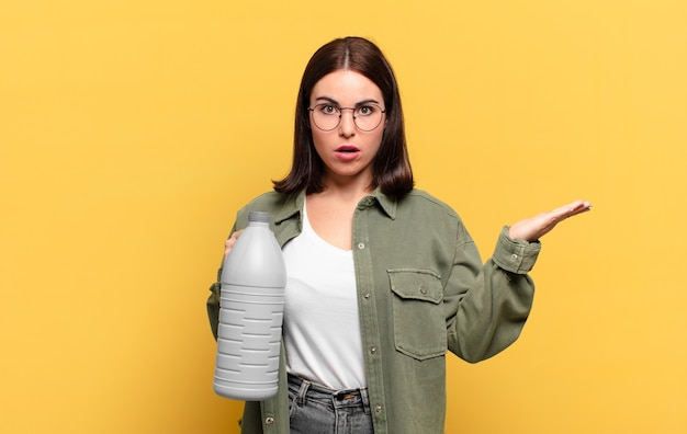 Mulher jovem e bonita parecendo surpresa e chocada, com o queixo caído segurando um objeto com a mão aberta na lateral