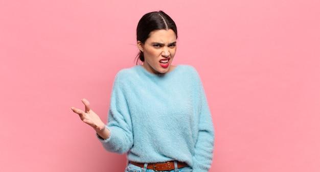 Mulher jovem e bonita parecendo zangada, irritada e frustrada gritando