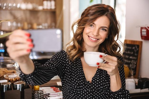 Mulher jovem e bonita passando um tempo em um café dentro de casa, segurando uma xícara, tirando uma selfie