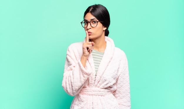 Mulher jovem e bonita pedindo silêncio e silêncio, gesticulando com o dedo na frente da boca, dizendo shh ou guardando segredo. conceito de pijama