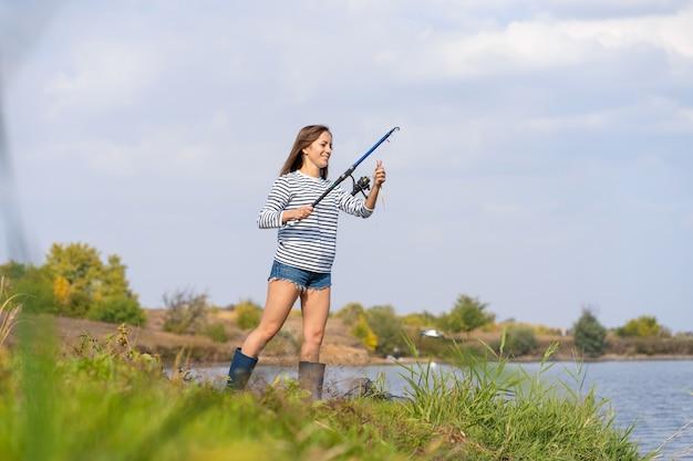Mulher jovem e bonita peixes no lago.