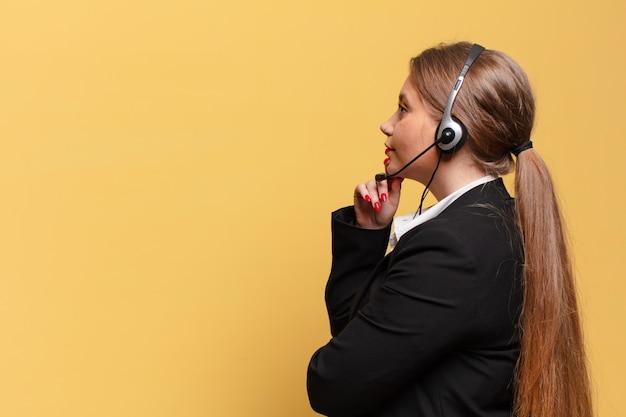 Mulher jovem e bonita pensando ou duvidando do conceito de operador de telemarketing