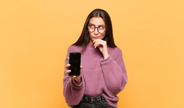 Mulher jovem e bonita pensando, sentindo-se duvidosa e confusa, com diferentes opções, imaginando qual decisão tomar. conceito de tela do telefone