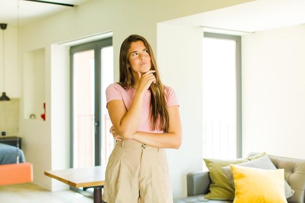 Mulher jovem e bonita pensando, sentindo-se duvidosa e confusa, com diferentes opções, imaginando qual decisão tomar