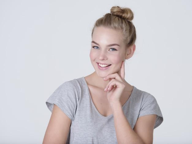 Mulher jovem e bonita pensativa com o dedo perto do rosto, isolado no fundo branco