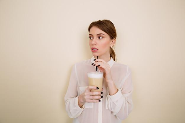 Mulher jovem e bonita pensativa em pé e tomando café com leite
