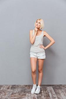 Mulher jovem e bonita pensativa em pé pensando sobre uma parede cinza
