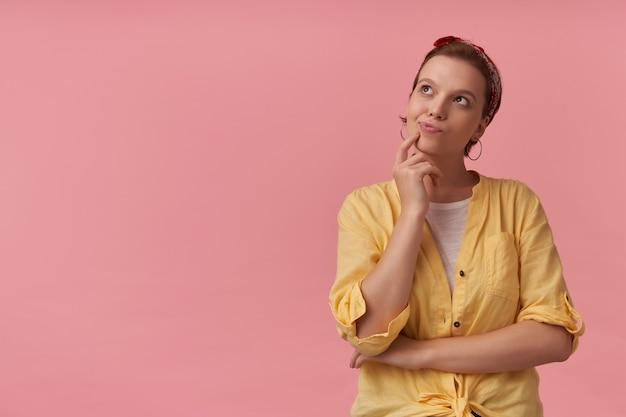 Mulher jovem e bonita pensativa em uma camisa amarela com uma faixa na cabeça em pé, pensando e olhando para o lado por cima da parede rosa