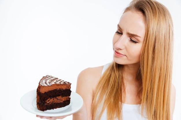 Mulher jovem e bonita pensativa olhando para um pedaço de bolo de chocolate sobre fundo branco