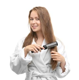 Mulher jovem e bonita penteando o cabelo depois do banho na parede branca