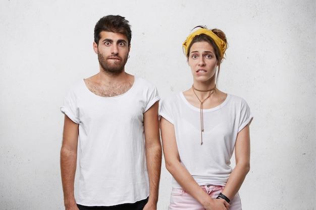 Mulher jovem e bonita perplexa em uma camiseta branca casual e homem surpreso com um penteado estiloso e cerdas mordendo os lábios